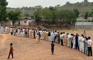 Pakistani voters queue outside a polling